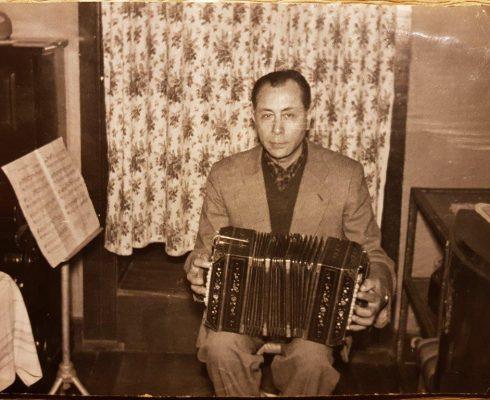 Alfonso Romero con su bandoneón, en su casa del Cerro Barón en calle Gonzalo de Berceo N° 168, Valparaíso. Al lado izquierdo se ve el piano que compró para su hija menor Silvia. Gentileza: Miroslav Yurac Romero.